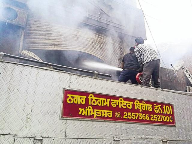 Fire-fighters from Amritsar trying to douse the flames at Patti where a showroom had caught fire earlier this week.