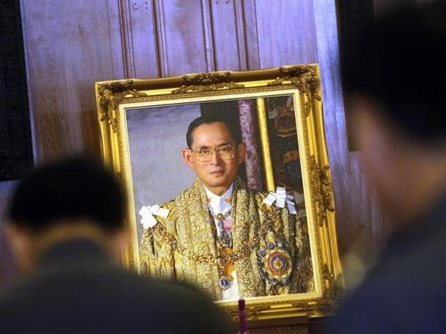 An old Thai woman offers prayer in front of a portrait of Thai King Bhumibol Adulyadej at Grand Palace in Bangkok, Thailand on Feb. 18, 2016. A mother of an activist was arrested after she failed to condemn insult of the royals by her son.