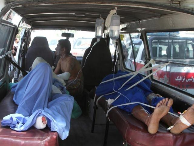 Injured men lie in an ambulance after a collision between two buses and a fuel tanker on the main highway linking Afghan capital Kabul to the southern city of Kandahar.