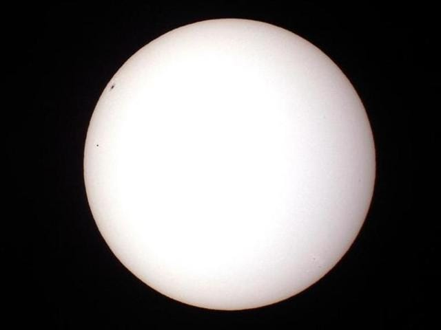 The planet Mercury (small dot on left) passes in front of the Sun and below a large sunspot as seen through a solar filtered telescope from Palm Beach Gardens, Florida.