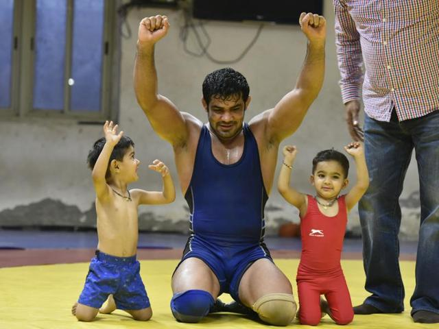 Indian wrestler Sushil Kumar seen with his 2 yeas old twins son Suvaran and Suveer during the practice session at Chhatarsal stadium in New Delhi on Friday.