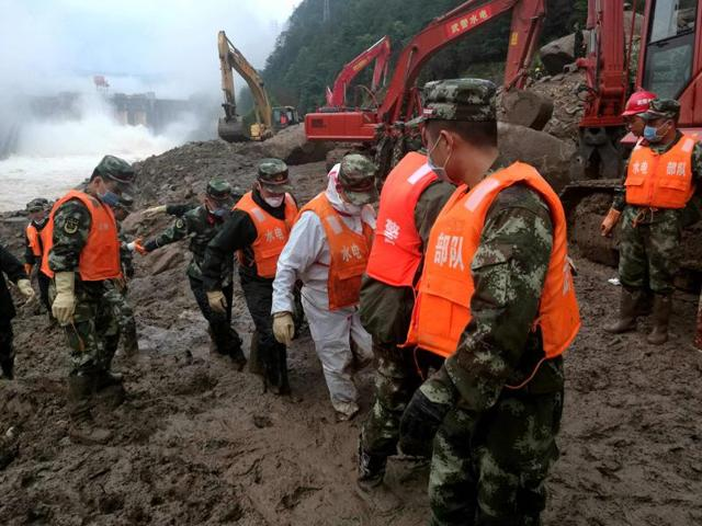 Rescuers stand in silent tribute for people killed during a landslide in Taining County, in China's Fujian province.