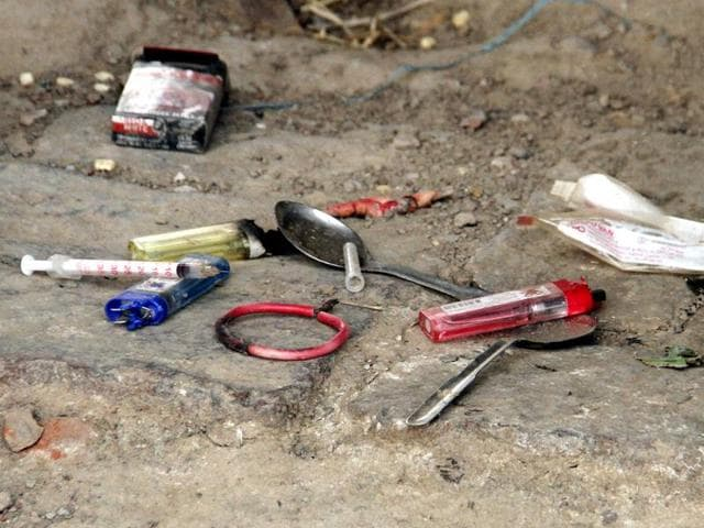 Syringes and lighters used to consume drugs in a field at Kul Gehna village in Ludhiana.
