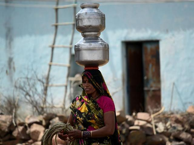A priest carries water in drought-hit Orchha , Bundelkhand
