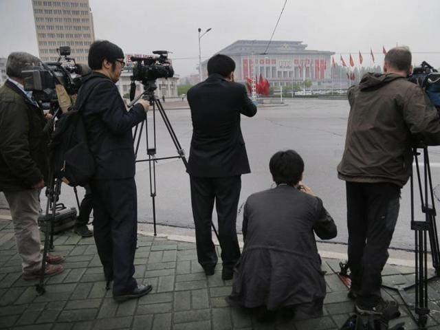 Foreign journalists photograph the April 25 House of Culture, the venue for the 7th Congress of the Workers' Party of Korea, in Pyongyang, North Korea.