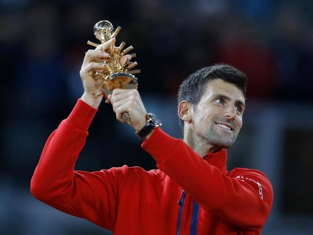 Novak Djokovic lifts his trophy after winning the Madrid Open tennis tournament final match against Andy Murray, in Madrid, Spain.