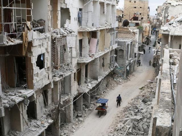 Residents walk near damaged buildings in Old Aleppo.