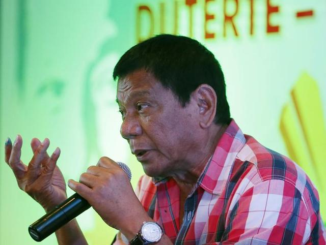 Front-running presidential candidate Mayor Rodrigo Duterte gestures during a news conference shortly after voting in a polling precinct at Daniel R. Aguinaldo National High School, Matina district, his hometown in Davao city in southern Philippines Monday, May 9, 2016.