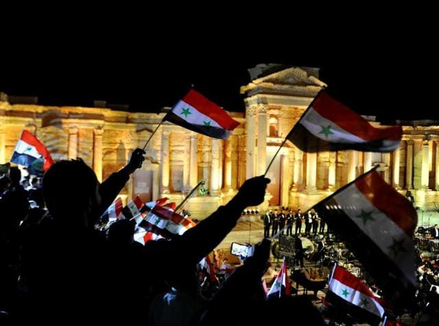 People wave Syrian national flags during a musical event called Gate of the Sun that was held to honour victims of the Syria's conflict in the amphitheater of the historic city of Palmyra, Syria.