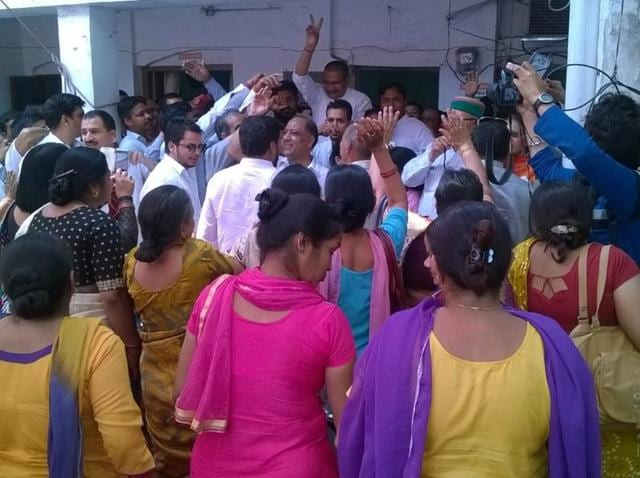 Congress workers celebrateafter the conclusion of the crucial trust vote in the Uttarakhand assembly