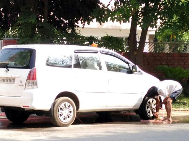 The driver of municipal corporation commissioner Anil Garg washing the latter's official vehicle with a pipe outside his residence in Bathinda on Monday.