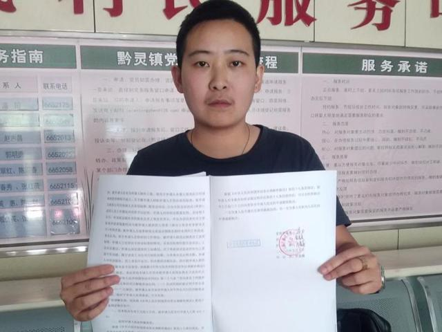 A transgender man who uses the name Mr. C to protect his parents from discrimination holds up the arbitration results while posing for a photo at a government office in Guiyang in southwestern China's Guizhou province.