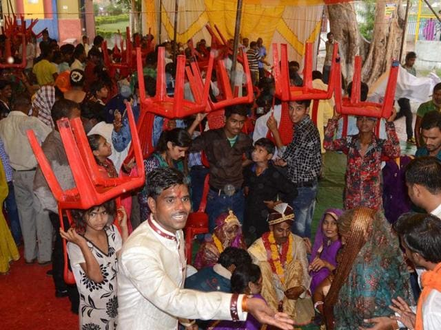 People guard a bride and groom with chairs as rainwater enters a marriage tent at Neelam Park in Bhopal on Monday.