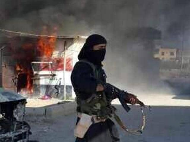 This file photo shows an image uploaded to an Islamic State, allegedly showing Shakir Wahib (L), and Abu Wahib, a leader of the Islamic State (IS) standing next to burning cars, at an undisclosed location in Iraq.
