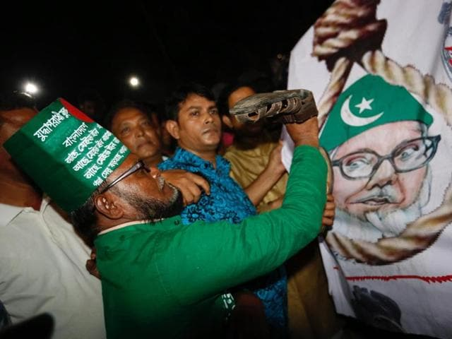 A Bangladeshi man throws a shoe at a Motiur Rahman Nizami poster to celebrate the execution of the Jamaat-e-Islami party's senior leader outside Dhaka's central jail, Bangladesh.