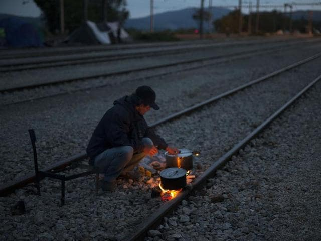 A man cooks on railway tracks at the northern Greek border point of Idomeni, Greece, on Tuesday May 10, 2016.
