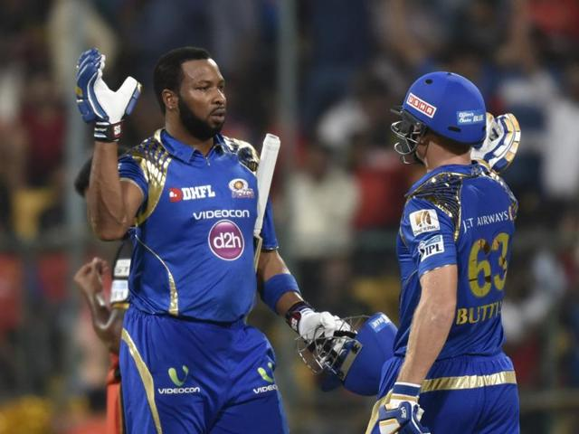 Mumbai Indians' Jos Buttler  (right) and Kieron Pollard celebrate after the win over Royal Challengers in Bengaluru on Wednesday.