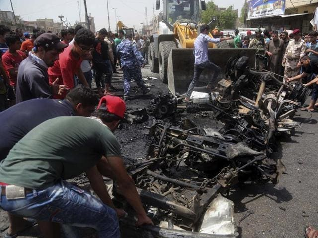 Security forces and citizens inspect the scene after a car bomb explosion at a crowded outdoor market in the Iraqi capital's eastern district of Sadr City on Wednesday.