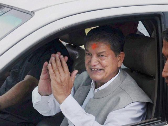Former chief minister Harish Rawat stands with  Congress MLA Yashpal Arya outside the assembly before the trust vote in Dehradun on Tuesday.