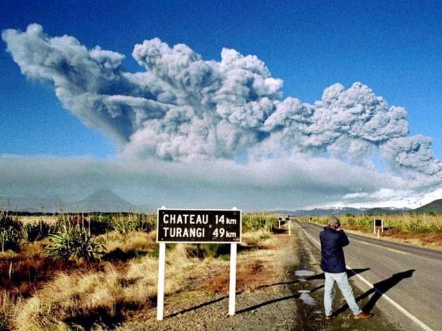 A tourist takes pictures of Mount Ruapehu as it erupts on June 18, 1996 in Tongariro National Park on the central North Island of New Zealand.
