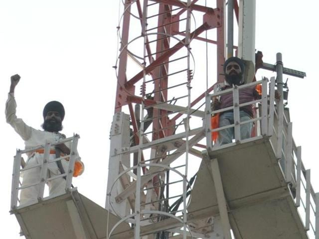Supporters of radical Sikh leader Dhian Singh Mand atop the BSNL tower in Patiala on Tuesday.