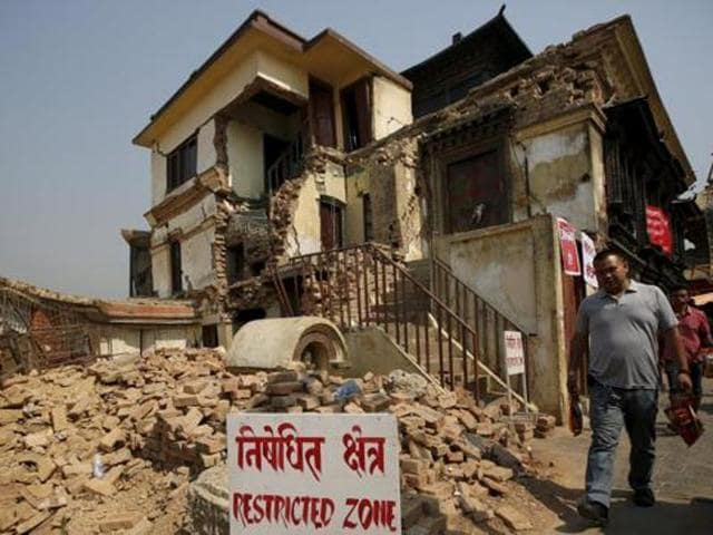 File photo of a man walking past the collapsed monastery at Swoyambhunath Stupa, a UNESCO world heritage site, a year after the 2015 earthquakes in Nepal.