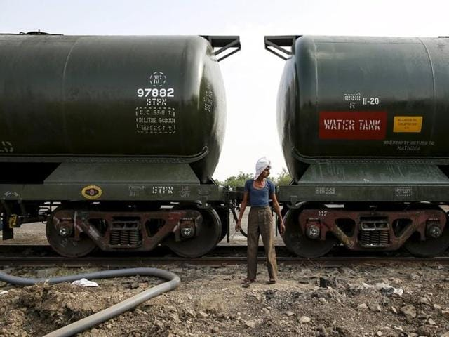 A worker stands in front of a tanker wagon carrying water at a railway station in Latur.