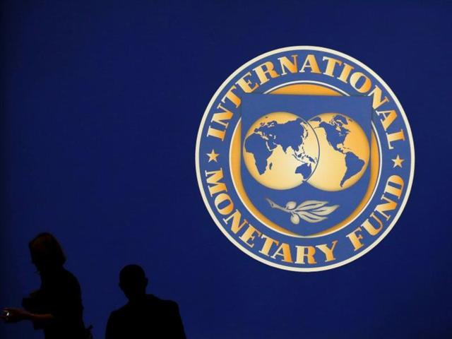Visitors are silhouetted against the logo of the International Monetary Fund at the main venue for the IMF and World Bank annual meeting in Tokyo in 2012.