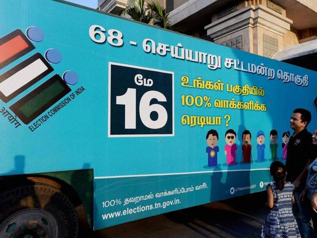 A family looks at a specially decorated bus that would spread awareness about the importance of voting in the forthcoming Assembly Elections, organised by Tamil Nadu Election Commission, in Chennai on Thursday.