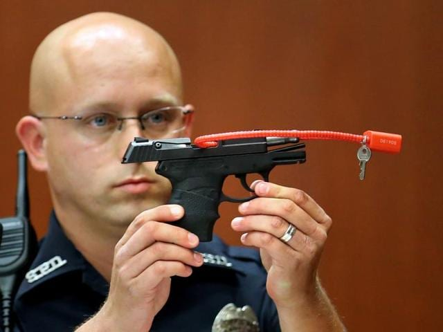 Sanford police officer Timothy Smith holds up the gun that was used to kill Trayvon Martin, while testifying during George Zimmerman's murder trial in Florida in 2013.