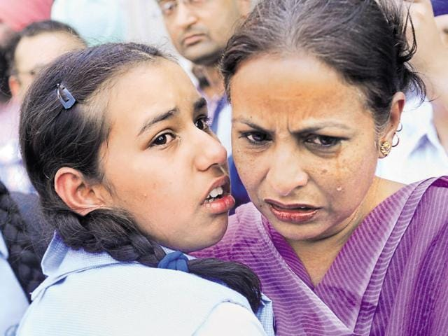 File photo of a woman and daughter crying after coming out of the library on April 12.