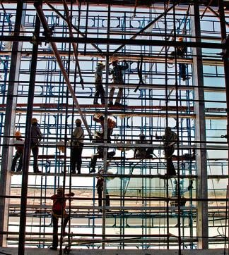 Indian labourers put sheets of glass in place of a new terminal bulding at the GMR Hyderabad International Airport
