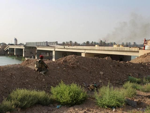 A fighter from the Iraqi pro-government forces looks towards the Albu Aitha bridge north of Ramadi following an attack a military source said was carried out by the Islamic State (IS) group, on May 12.