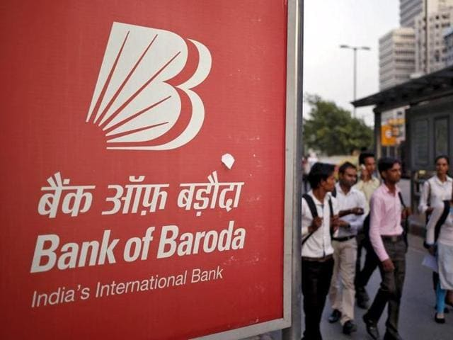 Commuters walk past an advertisement of Bank of Baroda on a busy street in New Delhi.
