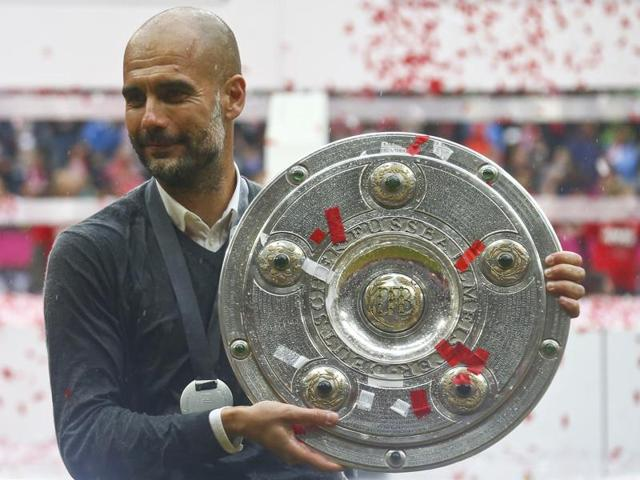 Bayern Munich's Pep Guardiola holds the trophy.