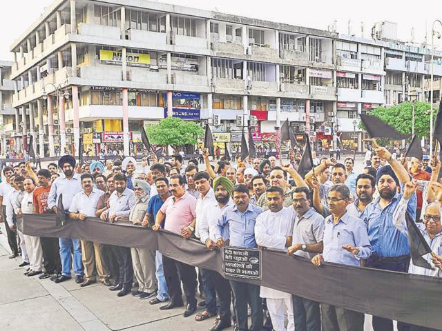 Traders and Congress leaders protesting in Sector 17 on Friday.
