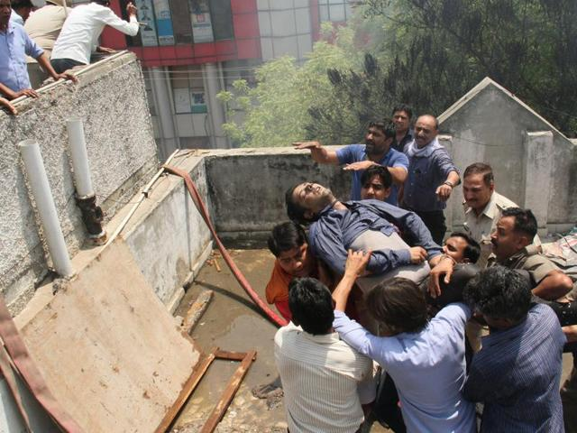 Local residents help rescue 11 employees of Indiamart who were stuck on the second floor of the building that caught fire on Saturday morning. The residents climbed to the roof of an adjacent building and used a ladder to reach the employees. One of them, Piyush Goel, who tried to jump over to the other building, missed and fell to his death.