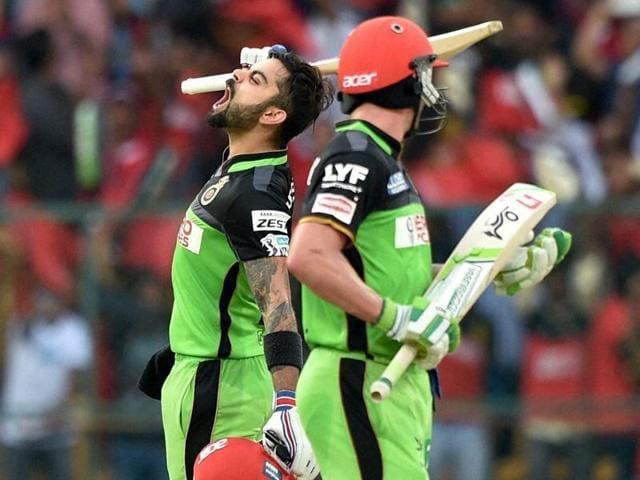 Virat Kohli celebrates his hundred as AB de Villiers watches.