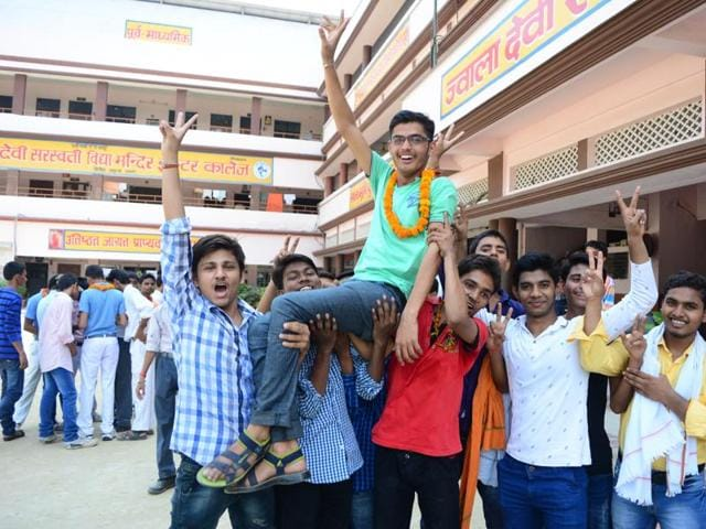 Students in Allahabad show the sign of victory after the results were declared.