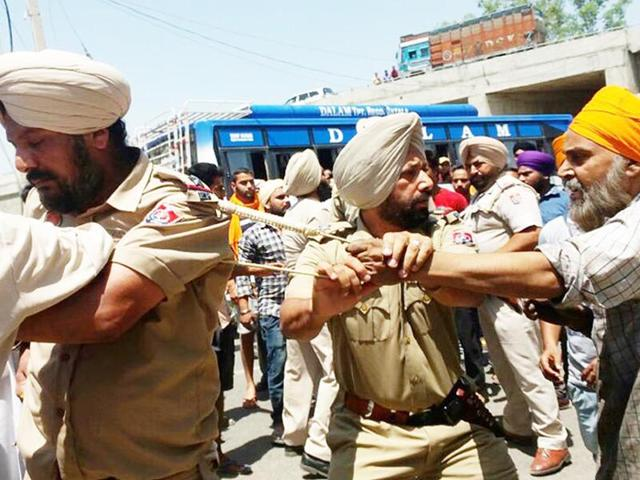 ASI Nirjit Singh tied to an electricity pole by agitated people in Batala on Sunday, May 15, 2016.