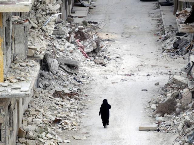 A woman walks past damaged buildings in the rebel-controlled area of Maaret al-Numan town in Idlib province of Syria.