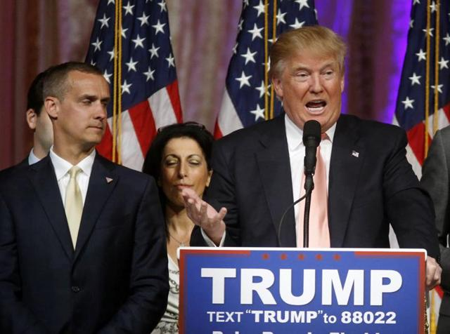 In this file photo, Donald Trump's campaign manager Corey Lewandowski , left, listens as Trump speaks in Palm Beach.