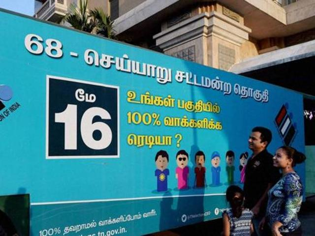 A family in Chennai looks at a bus designed to spread awareness about the importance of voting in the assembly elections.