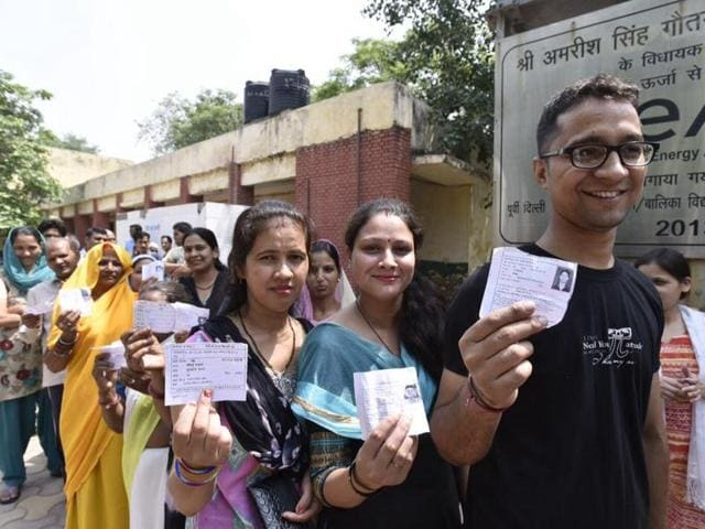 Voters queue up outside a polling station in Khichdipur in MCDby polls in New Delhi on Sunday.