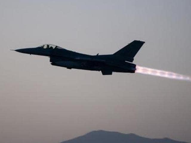 A Pakistani airforce F-16 plane flies over a Pakistani national flag.