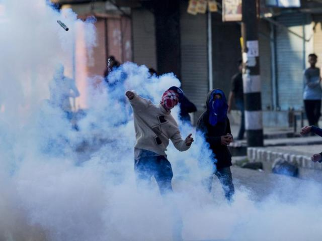 A masked protester throws back an exploded tear gas shell at Indian policemen during a protest in Srinagar on April 12.
