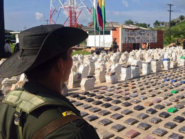 Handout picture released by the Colombian police showing a Colombian police officer standing guard over eight tons of seized cocaine in Turbo, Antioquia department, on May 15, 2016.