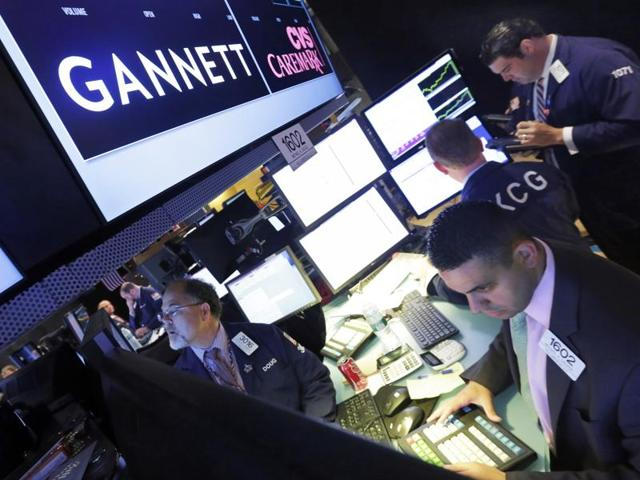 In  file photo, specialist Michael Cacace, foreground right, works at the post that handles Gannett, on the floor of the New York Stock Exchange.