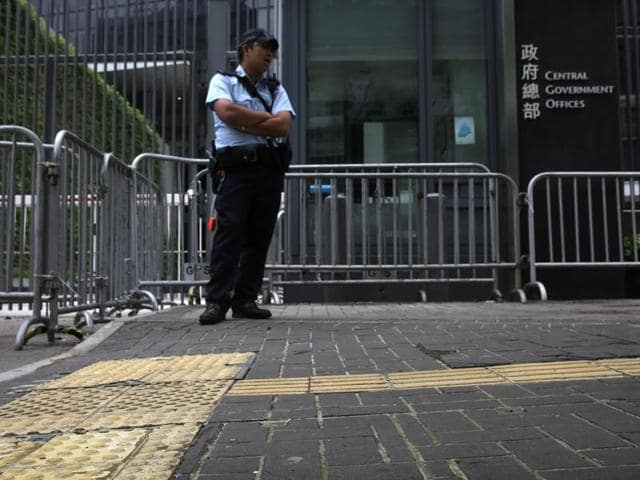 A policeman stands on pavement reinforced with glue to prevent the bricks from being dug up and used as projectiles during expected protests outside the central government offices in downtown Hong Kong.