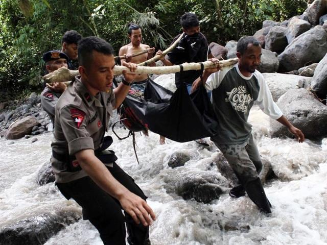 Indonesian police and villagers carry the body of a flash flood victim in Sibolangit, North Sumatra.